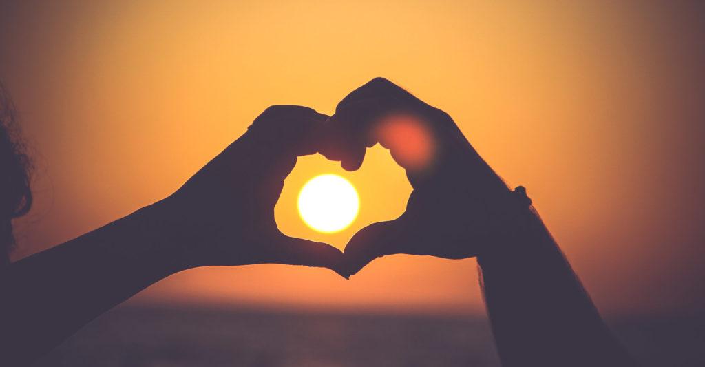 Hands making a heart shape around a sunset